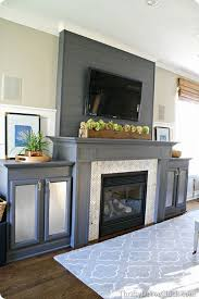 gray fireplace with marble surround and built ins for electronics