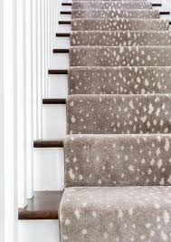 a gray animal print stair runner accents a white staircase boasting stained wood treads and white spindles