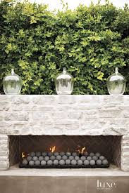 chic patio features a white stone fireplace accented with a taupe herringbone firebox topped with hand n jars