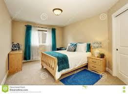 Ordentliches Beige Schlafzimmer Mit Türkisvorhang Und Hölzernem Bett