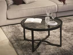contemporary crossy round coffee table in an industrial style with a glass top