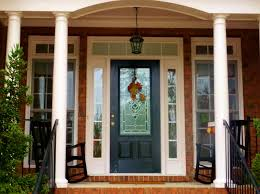 exterior black wooden door with glass on the middle between glass windows on the