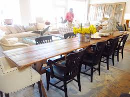 long farmhouse dining table made from reclaimed wood with flower centerpieces and 8 black wooden dining chairs and 2 white fabric cover dining chairs