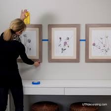 using painters tape to space frames evenly when hanging pictures