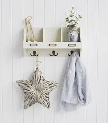 white wooden wall shelf with hooks