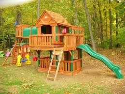 awesome cedar summit playset made of wood with green slide and swings plus bridge for kids