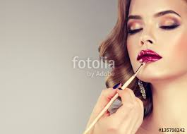 hand of make up master painting lips of young beautiful model makeup in