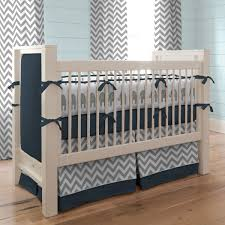 white wooden crib with dark blue also white gray zigzag pattern placed on the brown wooden