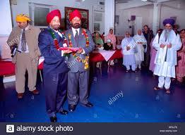 sikh wedding family members exchanging gifts garlands before wedding central gurdwara shepherds bush london england