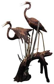 2 herons resting on a branch sculpture