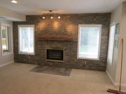 grey exposed brick stone accent wall combine with wooden fireplace mantel also modern track ceiling lighting
