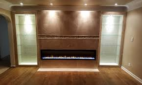 the entire wall was remodeled which included the framed glass shelves a full wall of tile along with the fireplace installation this was a project we were