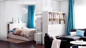 Ikea - A living space divided into a bedroom and living room by a bookcase