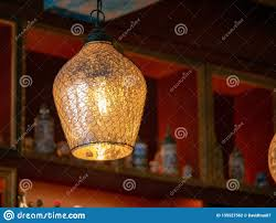 Glass And Wire Lamp Cover On A Hanging Light Bulb In Dark Bar Stock
