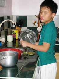boys washing dishes. Perfect Boys A Boy Washes A Bowl At The Kitchen Sink And Boys Washing Dishes O