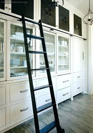 butlers pantry in an all white kitchen rolling library ladder to reach high storage designed by
