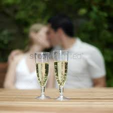 1696810 wine glass cheers two glasses of champagne with couple kissing in the background