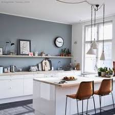 bluegrey wall with white cabinets and warm brown chairs kitchens blue walls g7 with