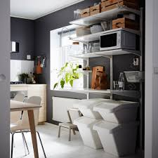 Dark grey kitchen with wall-mounted white shelves with waste sorting units  underneath.