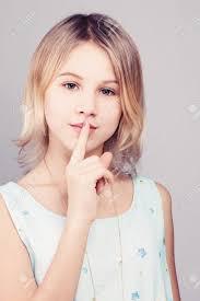 金髪ボブの髪型の少女十代の少女は秘密のジェスチャーで彼女の唇に