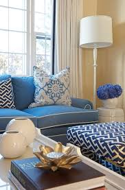 chic blue living room with blue sofa with white piping accented with white and blue pillows placed in front of window covered in off white curtains accented