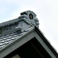 a carved stone roof finial rides the ridge of a house in japan these were