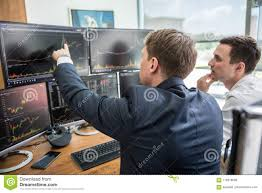 Stock Brokers Stock Brokers Looking At Computer Screens Trading Online Stock