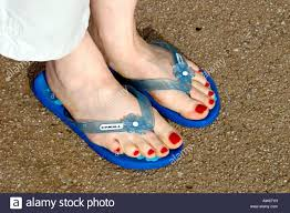 red painted toenails and flip flops stock image