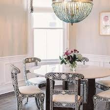 black and white bone inlay dining chairs with turquoise blue beaded orb chandelier