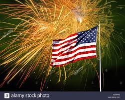 An American Flag In Front Of A Fireworks Display On July The