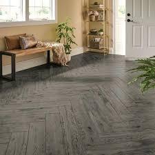 luxury vinyl plank imitating gray hardwood flooring installed in a herringbone pattern country grey