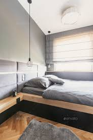 grey sheets and cushions on wooden bed in minimal bedroom interi stock photo images
