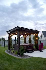 Timber frame ShadeScape DIY pergola kit from Western Timber Frame  installed over backyard hot tub with outdoor lighting.