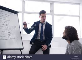 Two Work Colleagues Discussing Strategy In Front Of A Flip