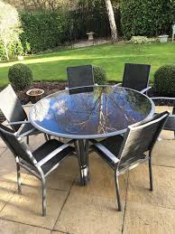 round glass garden table and six matching chairs