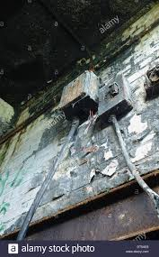 fire damage remains of mains electrical armored wires fuse box fire damage remains of mains electrical armored wires fuse box junction over rusty steel lintel on wall peeling paint and soot