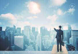 businessman standing on a roof and looking at future city stock photo