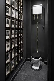 black bathroom. We Also Appreciate The Clean Lines From High Black Skirting, As Well Symmetrically-framed Posters. Bathroom A