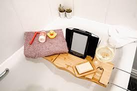 wooden bath caddy over bathtub shelf with a wine glass