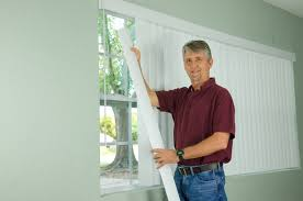 man hanging blinds