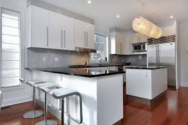 modern kitchen with absolute black granite counter peninsula cherry wood floors and piston stools with