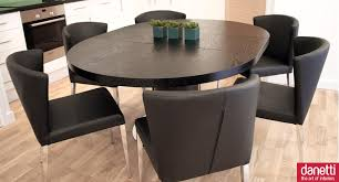 modern dining room design with black expandable round dining table and black dining chairs also centerpiece