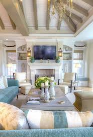 Cottage Living Room with Exposed beam ceiling, Distressed Ceramic Pillar  Holders Hardwood floors, Cement fireplace