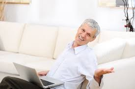 lance writing work from home online community writers relaxed senior man laptop on sofa smiling