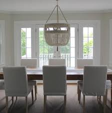 chic dining room features a ro sham beaux frankie malibu white swirl pendant illuminating a long plank dining table lined with white slipcovered dining
