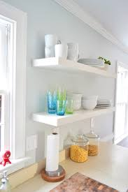 two long ikea floating shelves in a kitchen holding colorful cups and stacks of white dishware