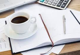 office agenda coffee cup at office with financial papers agenda and calculator