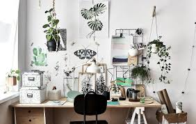 artwork and inspiration displa on a wall above a wooden desk and black chair