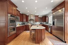 dark cherry hardwood cabinetry light toned hardwood flooring white cream marble countertops and stainless steel appliances