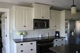 two toned kitchen with black countertops and white cabinet housepluz
